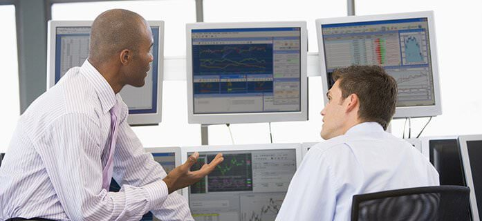 Two men looking over financial data on computers